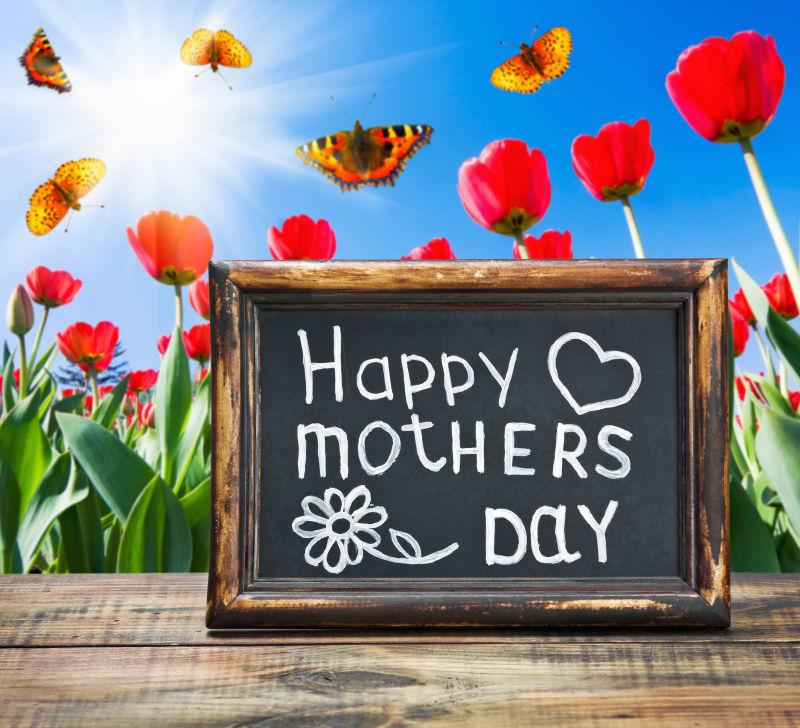 美丽的鲜花背景下木板上的母亲节快乐小黑板