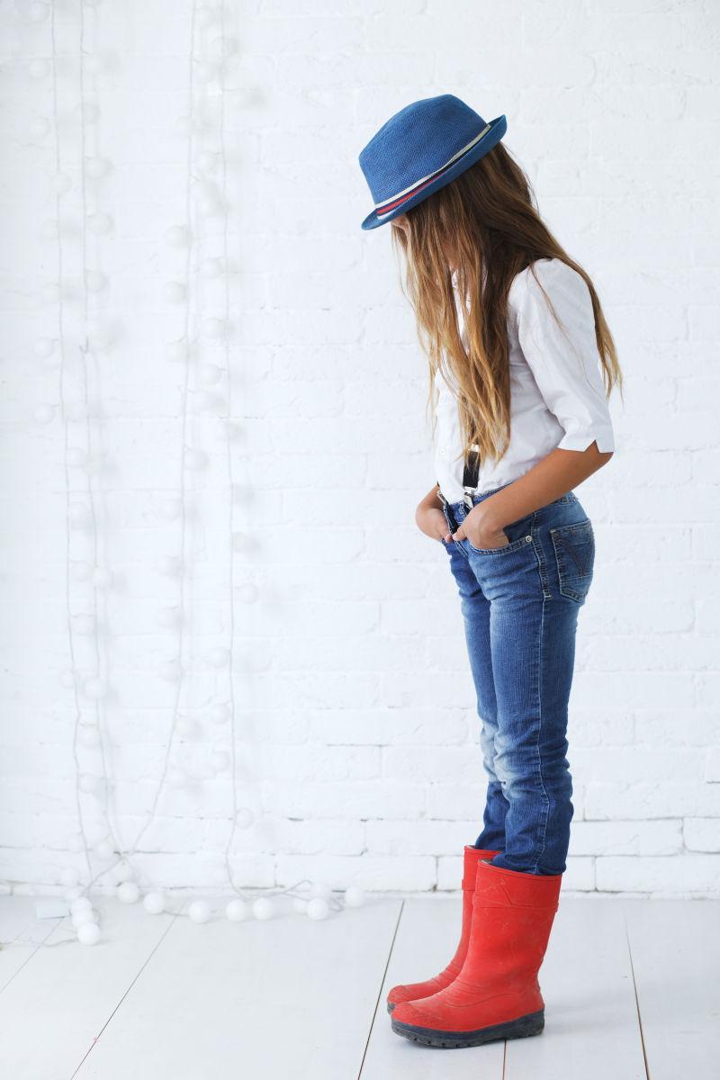 室内穿着红色皮靴的低着头的小女孩