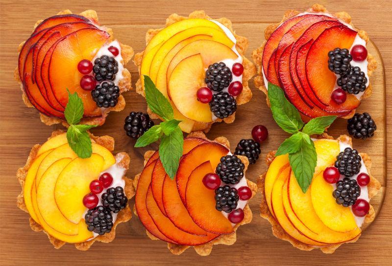 木桌上的红色和黄色水果片装饰的奶油馅饼