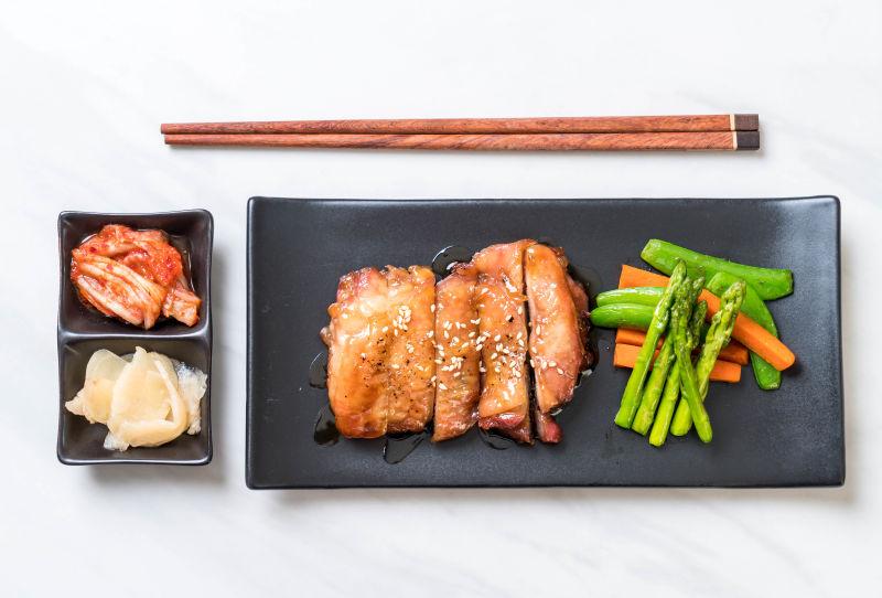 黑色盘子里的烤肉和配菜