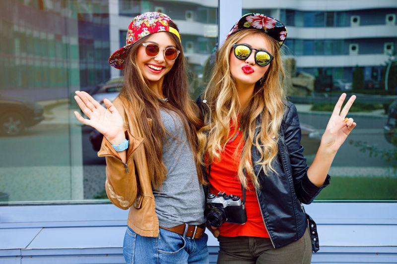 穿着皮夹克摆着鲜艳的帽子和太阳镜的两个最好的朋友