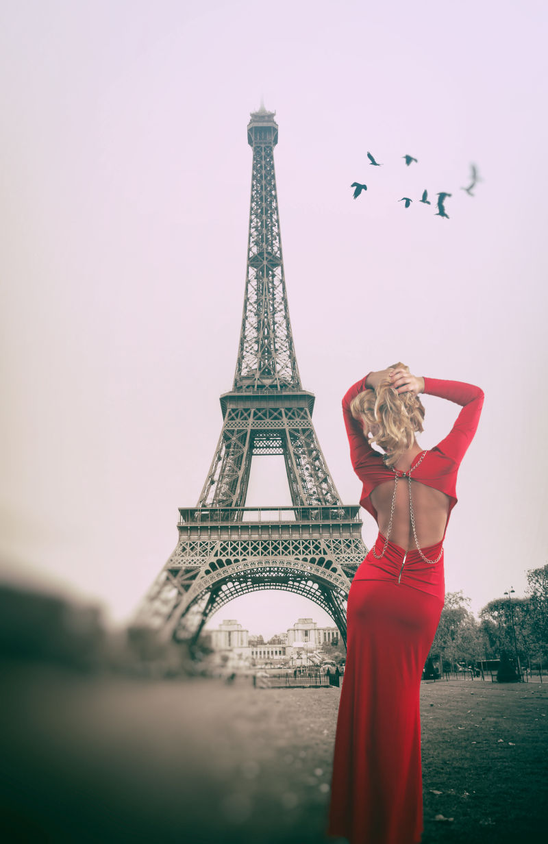 穿着红色礼服的美女面对着铁塔