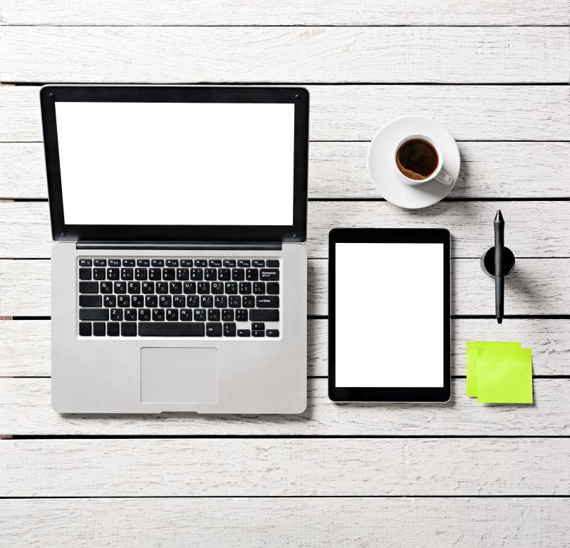 白色木桌上空白屏幕的笔记本电脑平板电脑和一杯咖啡