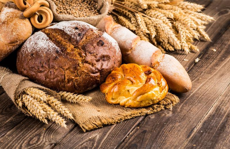 旧木桌上的麦穗和小麦面包