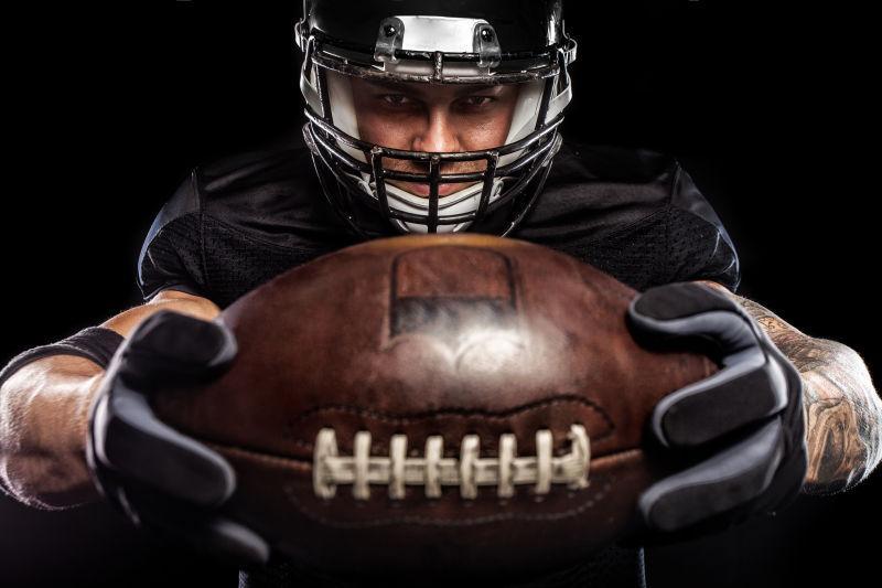 黑色背景下的美式足球运动员