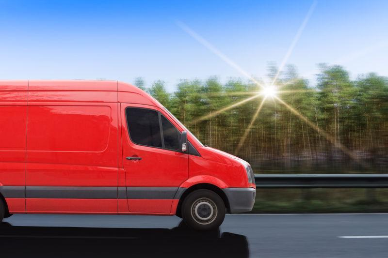 有阳光的蓝天下道路上的红色的货车