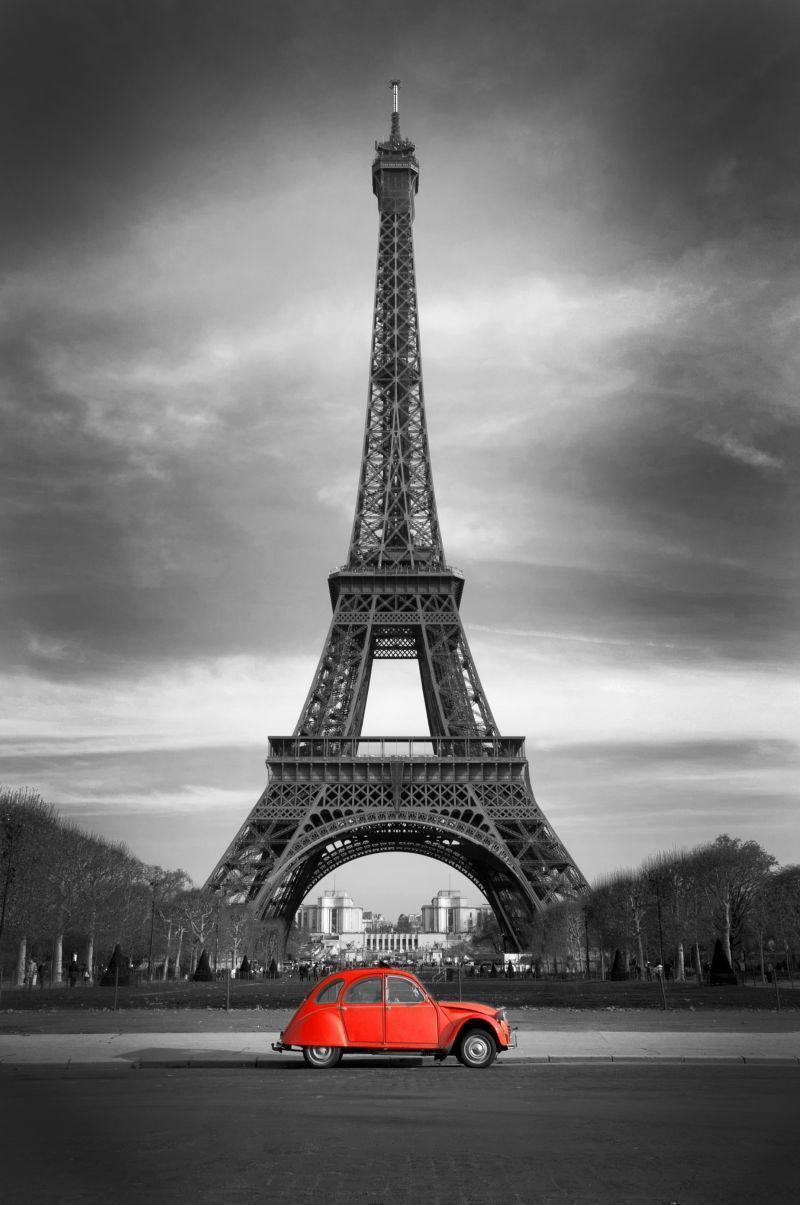 巴黎埃菲尔铁塔前边行驶着一辆红色轿车