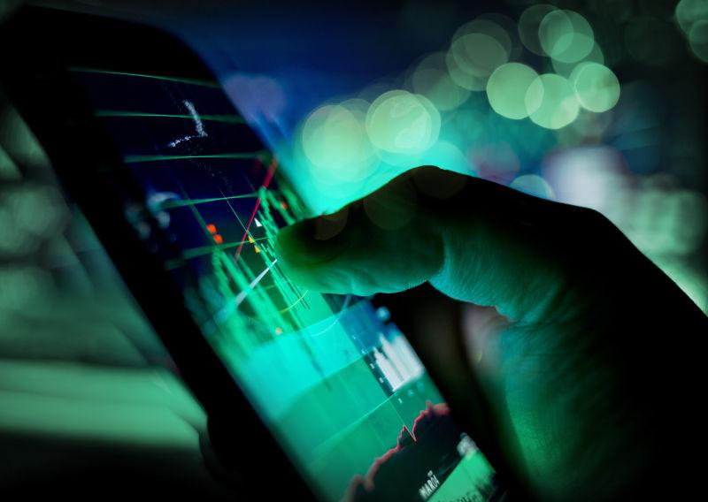 用手指触碰移动设备上的股市走势图