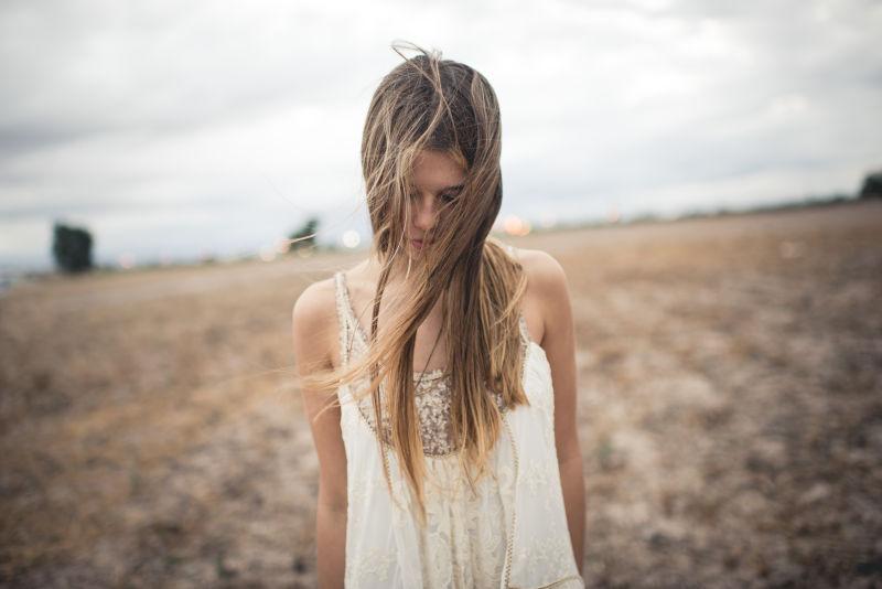 夏季田野里的美女低头享受风的抚摸