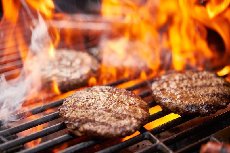 在烤架上烹饪的汉堡包和热狗