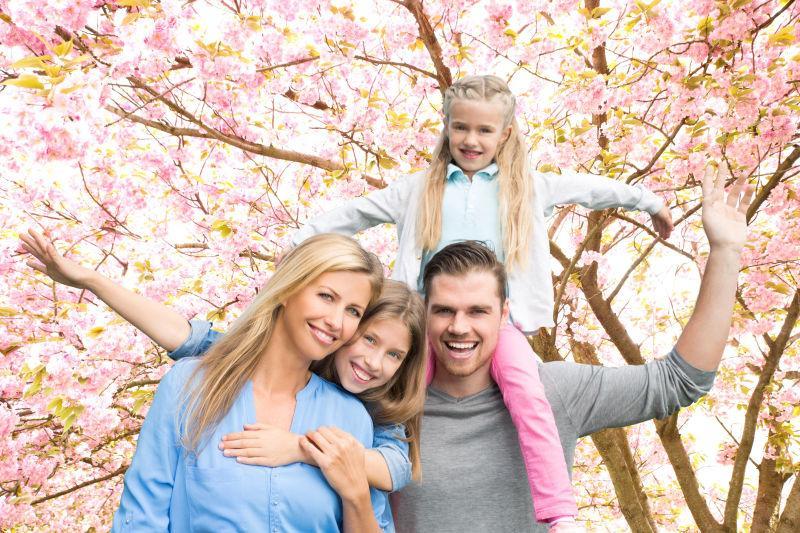 在开花的春季树林中的开心的一家人