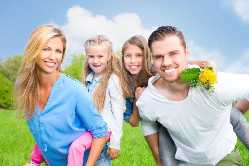 蓝天下绿色草地上开心的玩耍的一家人