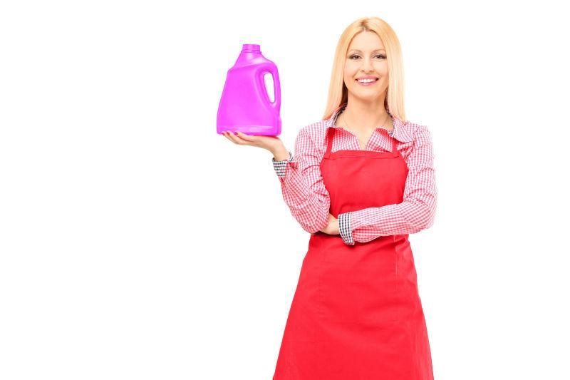 白色背景下拿着洗涤剂的家庭主妇
