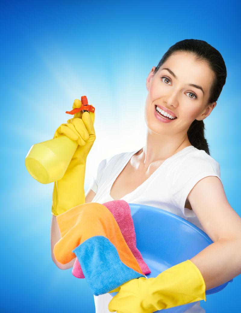 蓝色背景下拿着喷雾清洁的女人