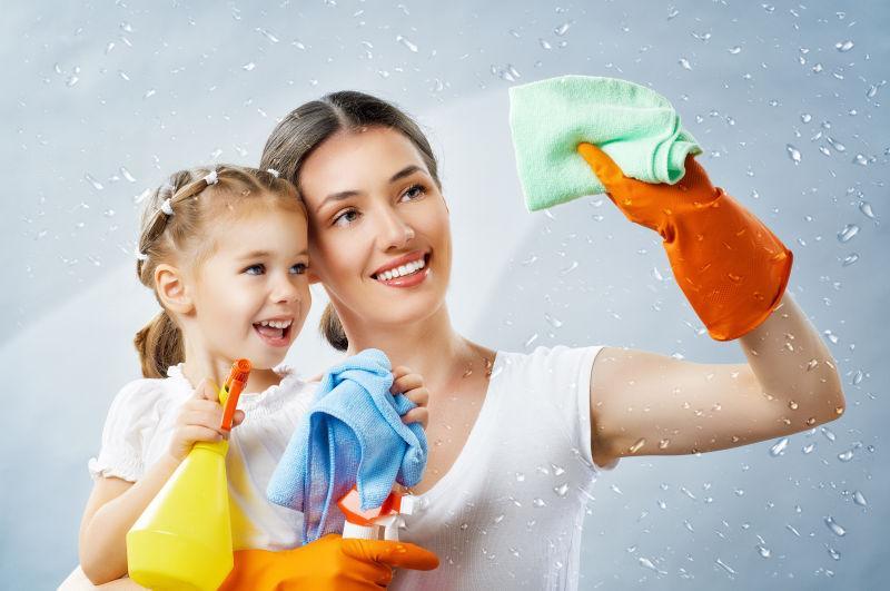 和孩子一起打扫卫生的微笑的家庭主妇