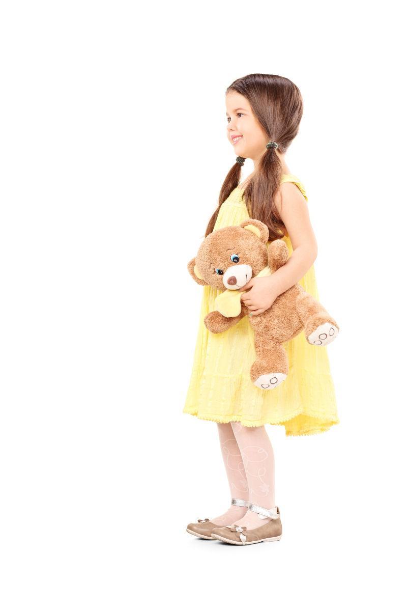 白色背景上的小女孩抱着玩具熊