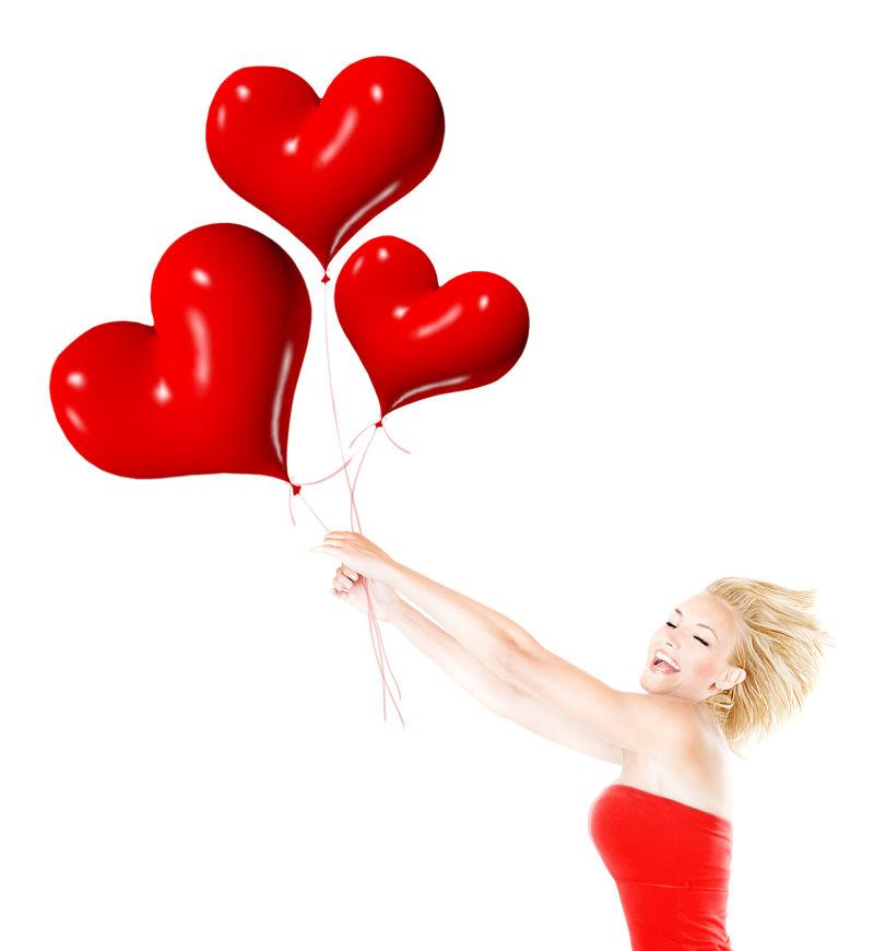 美女开心的拿着红色心形爱心气球