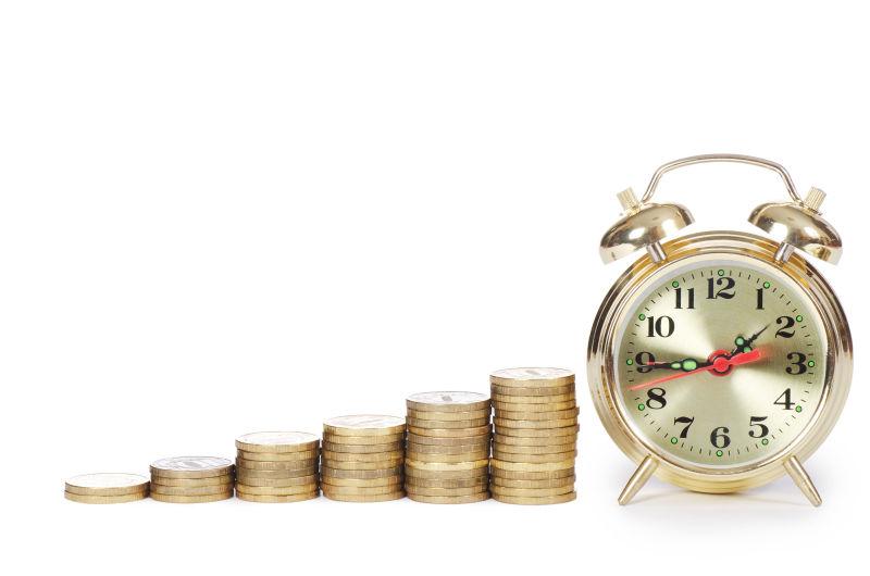 白色背景下的闹钟与一堆上涨的硬币