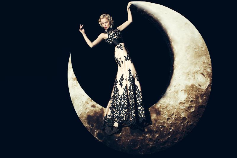 黑色背景上站在月亮上的复古美女