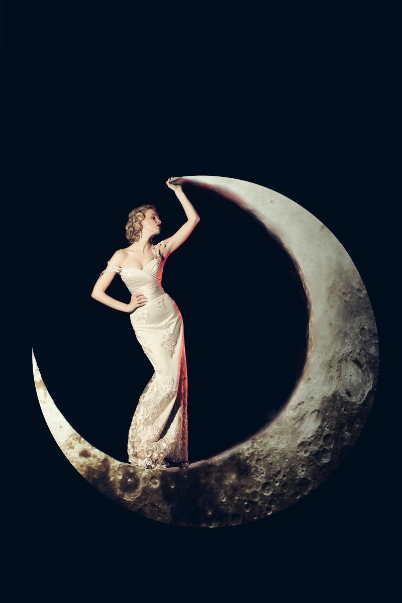 黑色背景上站在月亮上的美女