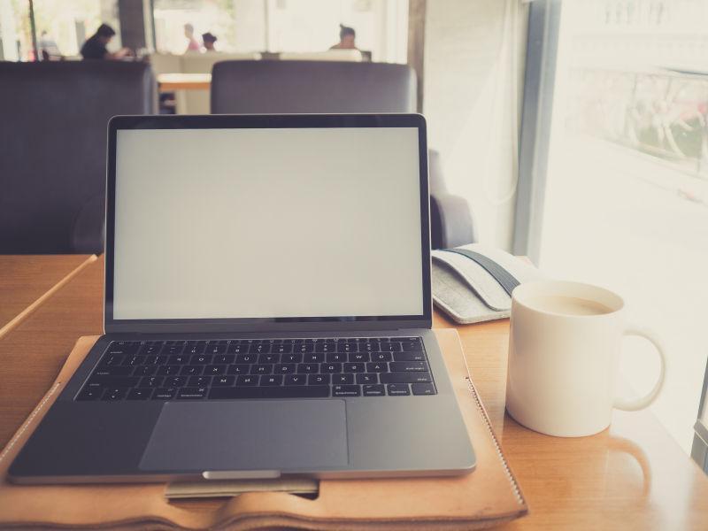 咖啡桌上的空白屏幕笔记本电脑