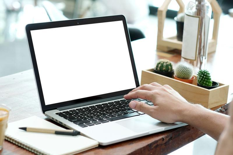 男子手在空白屏幕笔记本电脑上打字
