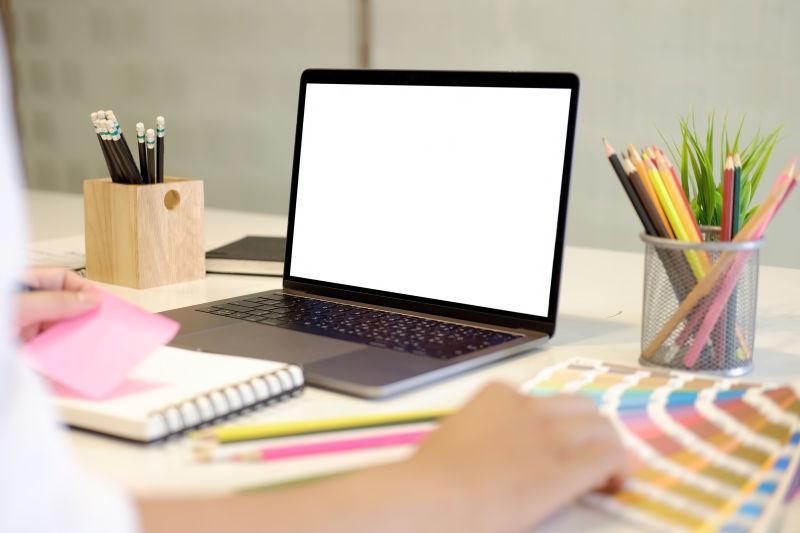 绘画设计师办公桌上的空白屏幕笔记本电脑