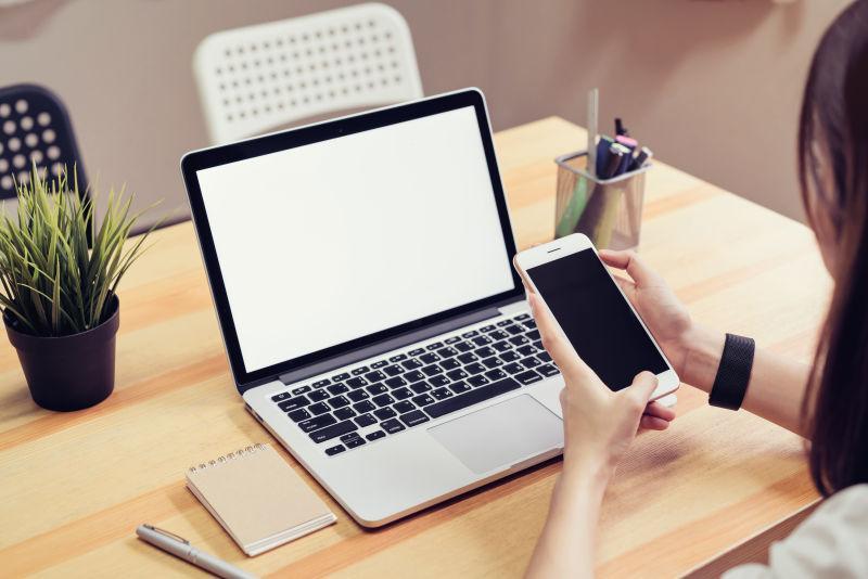女人拿着一部手机和桌上的一台笔记本电脑