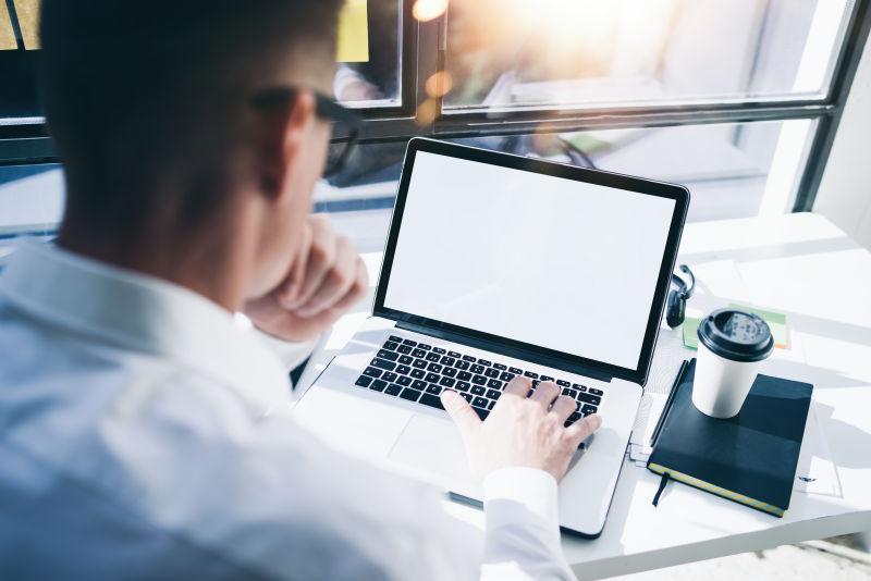 用笔记本电脑工作的办公桌前的男人
