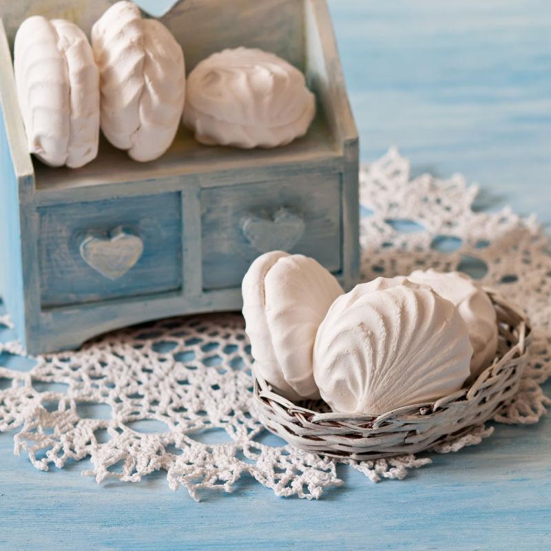 蓝色背景下花边餐巾上的白色棉花糖