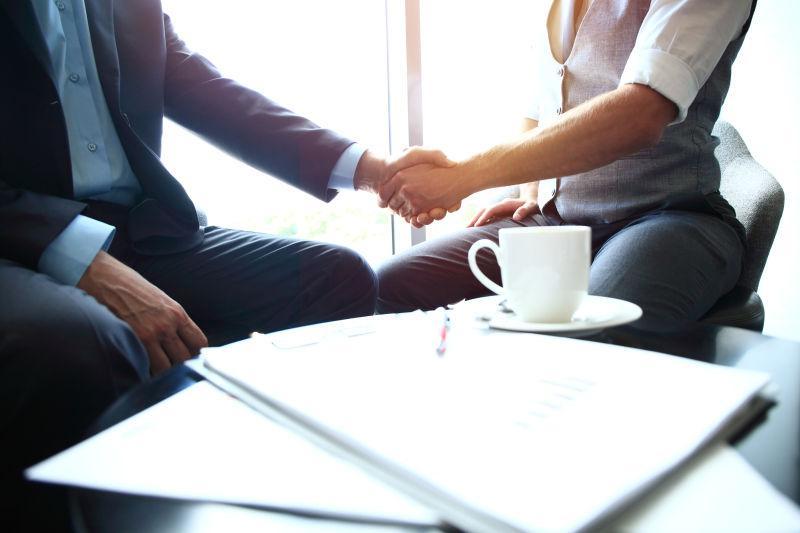 放着合同和咖啡杯的办公桌边握手的商人