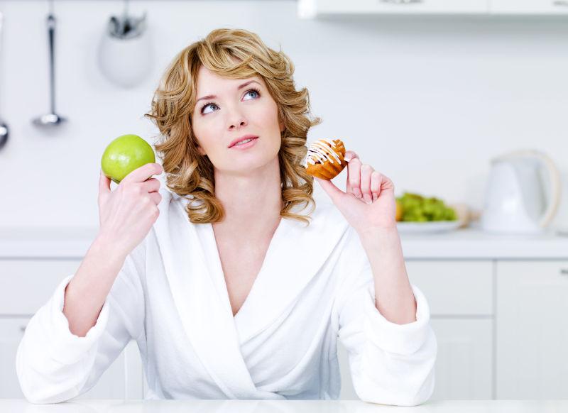 女人在厨房拿着蛋糕和苹果选择
