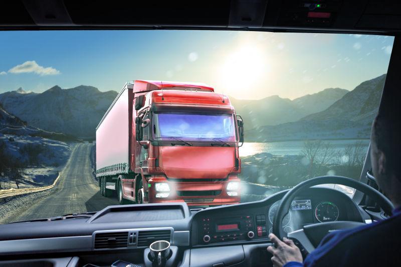 群山和阳光的背景下的公路上的红色卡车