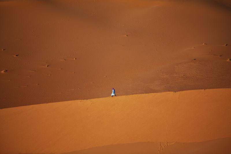 金黄色的沙漠上行走的一个人