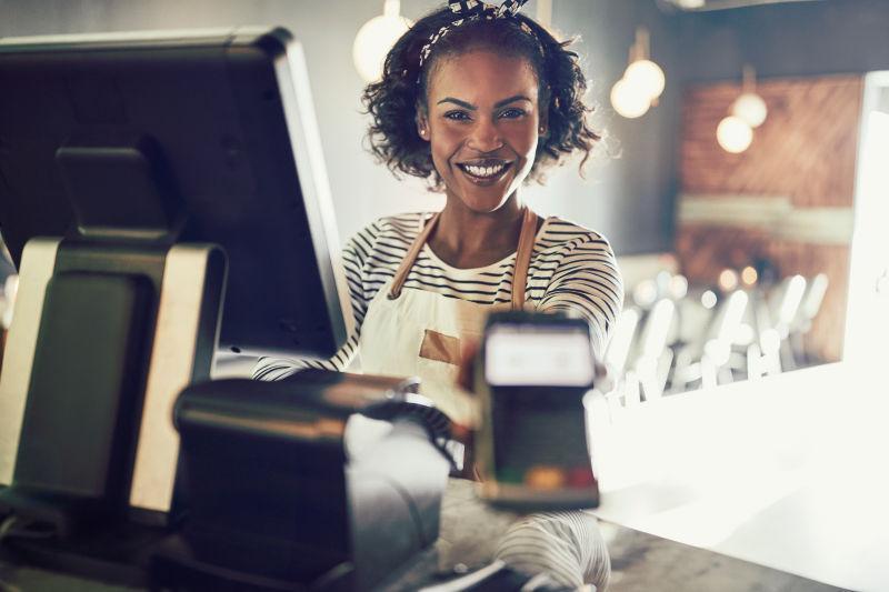 微笑的小酒馆女服务员拿着电子卡付款