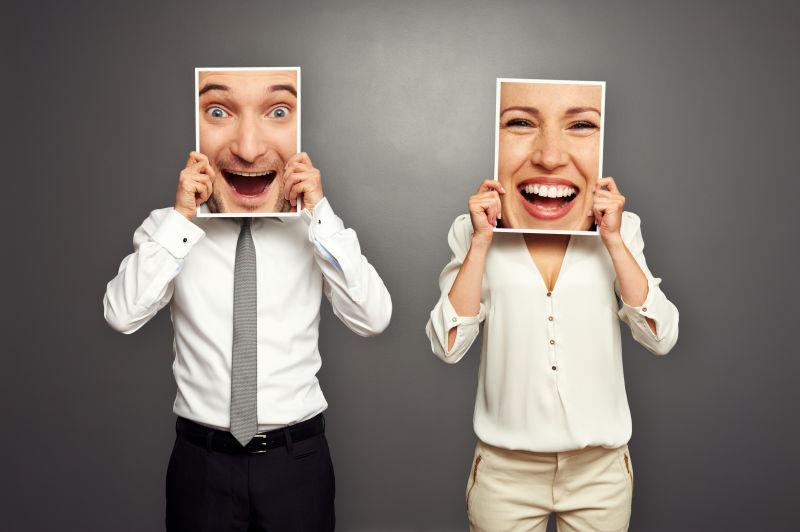 灰色背景中举着微笑框架的男人和女人