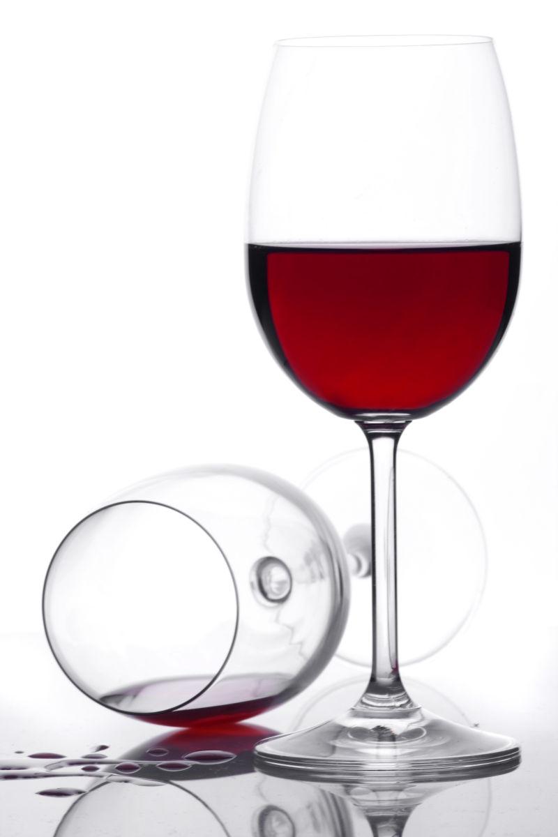 一杯倒着的红酒和一杯放着的红酒