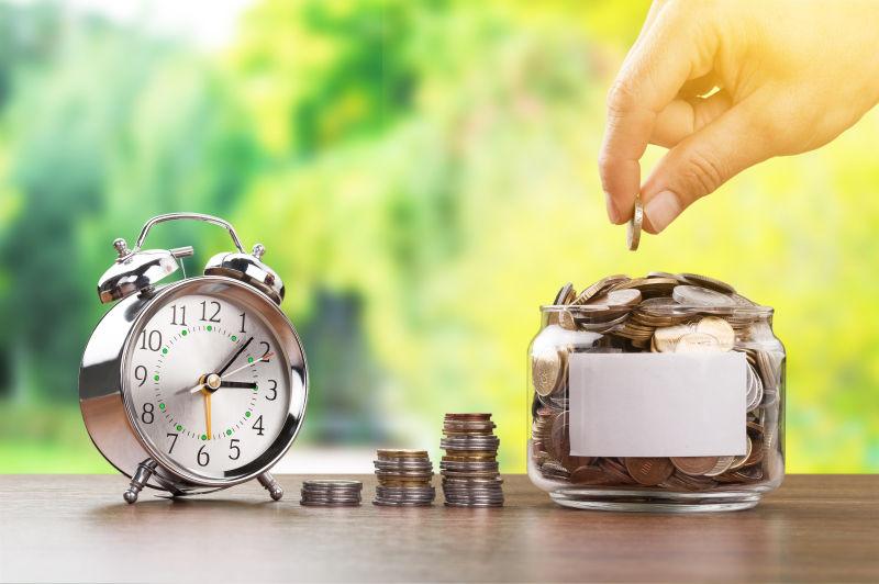 木制桌上的时钟和储存金钱