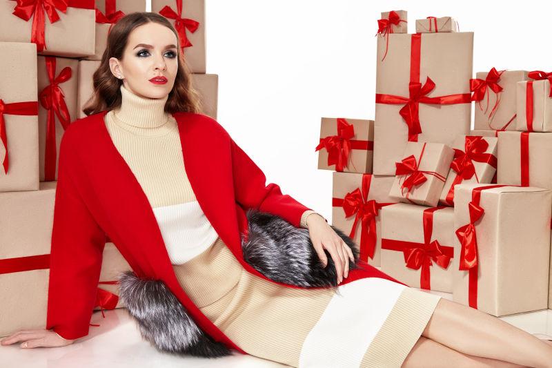 坐在一堆礼品盒旁边的时尚美女