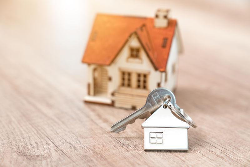 房子钥匙在一个房子形状的钥匙链搁置在木地板上的概念
