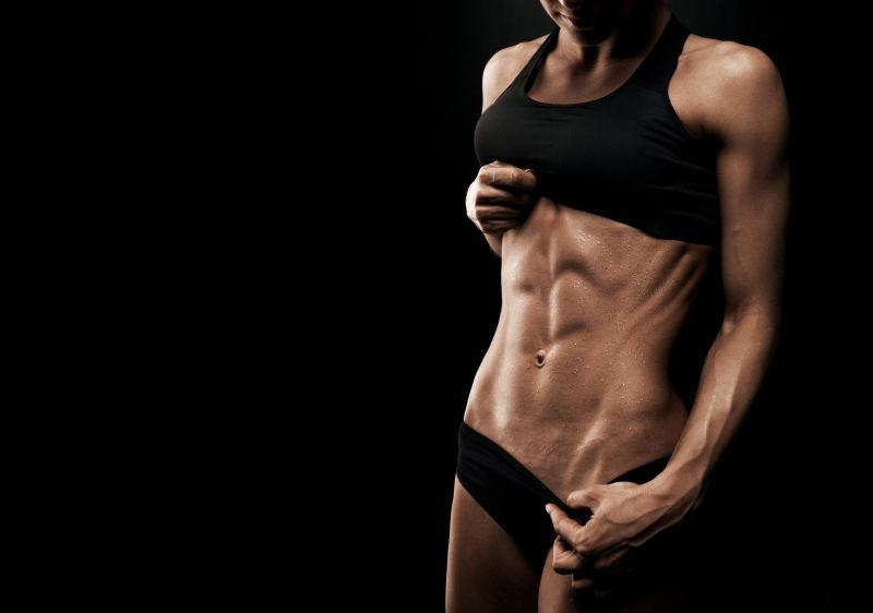 黑色背景上有腹肌的运动女性