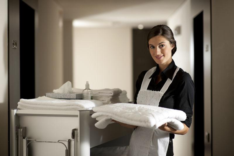 正在送浴巾的酒店客房女服务