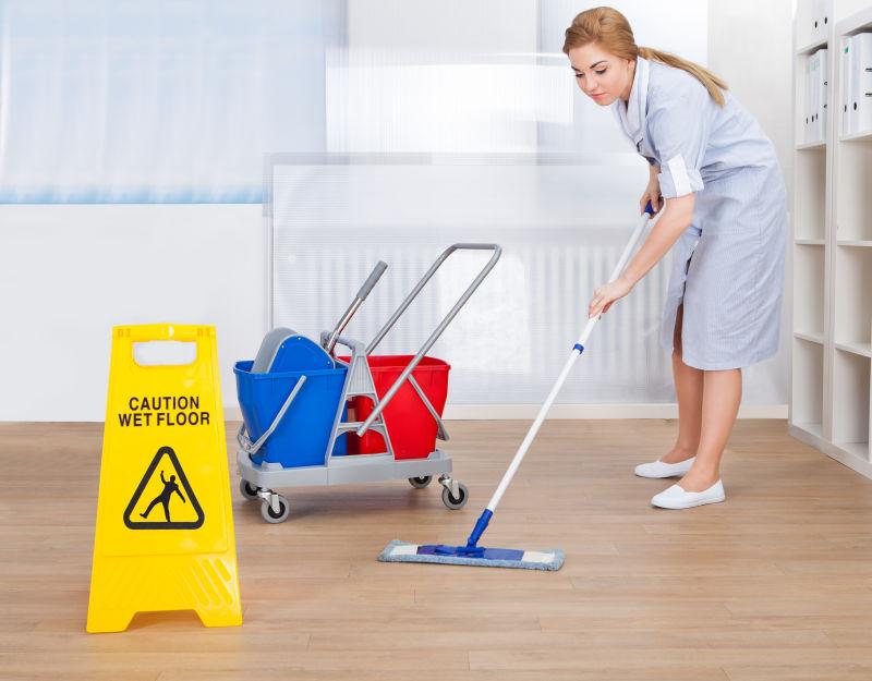 正在用拖把清洁地板的年轻女佣