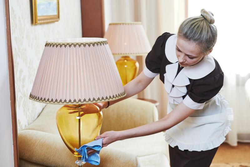 在擦拭台灯的酒店客房服务员