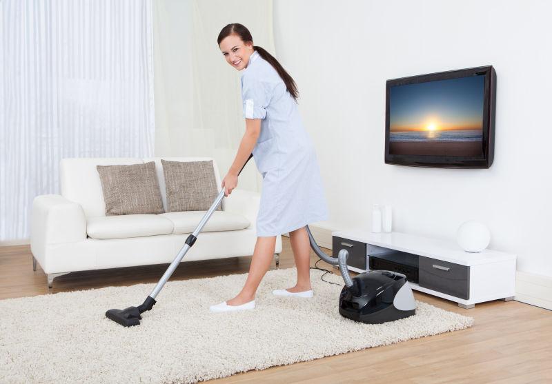 用吸尘器清洁地毯的女人