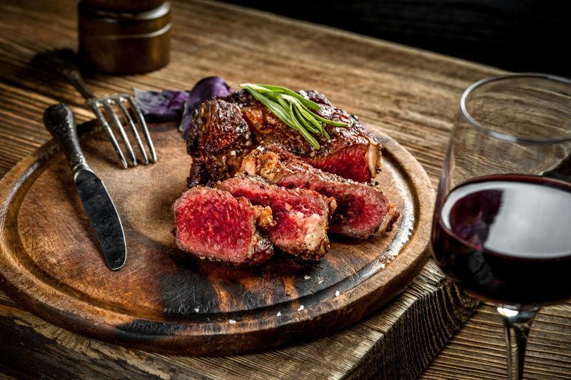 烤红牛牛排配红酒图片-烤红牛牛排和红酒配香草和香料在木桌上素材-高清 ...
