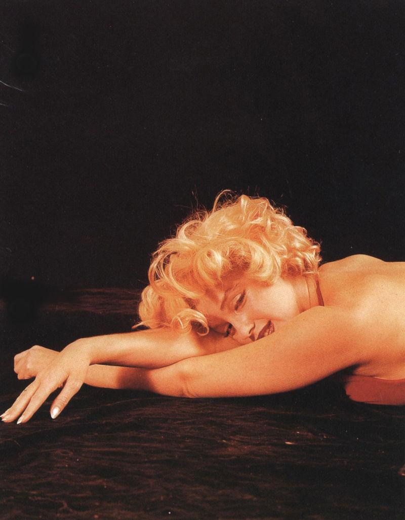 黑色背景下趴着的金发美女