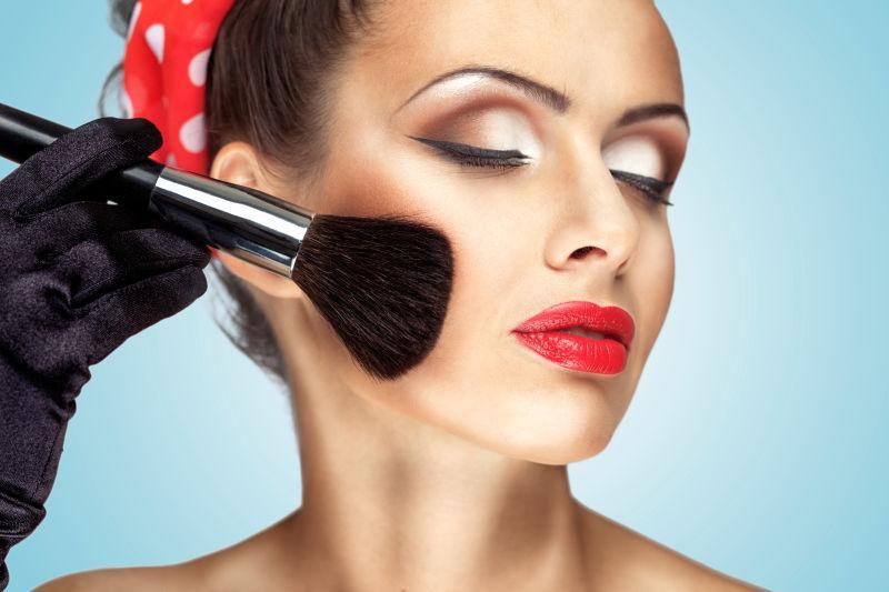 魅力少女用时尚化妆画她的脸颊用刷子