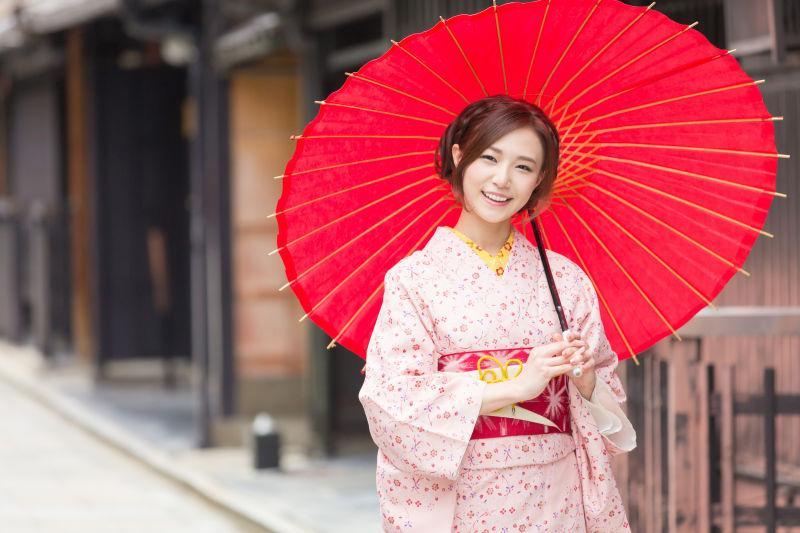 微笑的撑着红色遮阳伞的日本艺伎