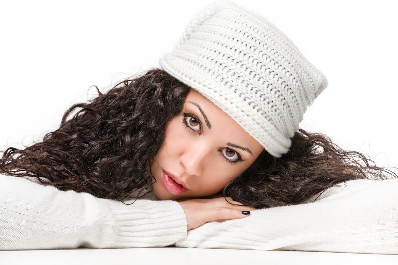 白色背景下迷人的戴着帽子的美女